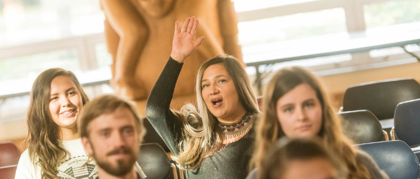 Woman raising her hand in the First Nations Longhouse